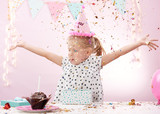 Lovely birthday girl trowing colorful confetti in the room. Cute child in pink cap having fun on party.