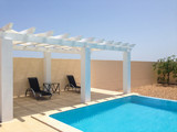 White poolside pergola, gazebo providing shade on a terrace patio area next to a swimming pool. Mobilestock.
