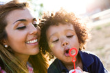 Beautiful young mother with her son blowing soap bubbles in the