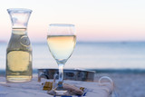 The carafe of white wine and a glass of wine on the beach, sunset, dinner by the sea, holiday, romance. Holidays in Greek wine in Greece.
