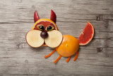 Amusing squirrel made of fruits on wooden background
