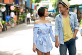 Cheerful Asian couple in love holding hands