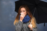 Woman sneezing handkerchief outdoor in autumn