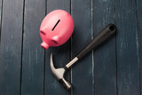 Piggy bank and hammer on wooden table