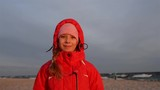 Beautiful smiling teenage girl in a red jacket on a background of a winter Baltic coast.