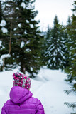 Woman walking in winter forest on snowy trail. Girl hiking in white winter woods.
