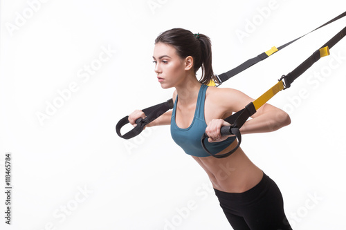 Upper body excercise concept. Image of beautiful woman exercising with suspension straps alone in studio. TRX concept isolated on white background.