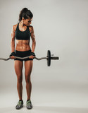 Woman with muscular physique lifting barbell