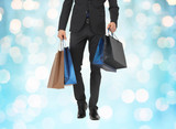 close up of man in suit with shopping bags