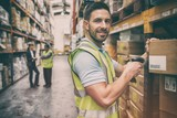 Warehouse worker scanning box while smiling at camera - 118484936