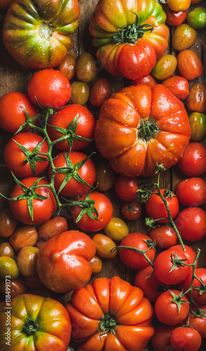 Colorful tomatoes of different sizes and kinds, top view, vertical - 118499173