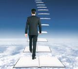 Businessman climbing book ladder