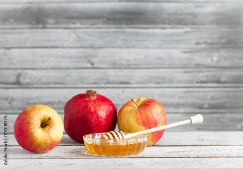 Pomegranate, apples and honey on white wooden table - traditional symbols of the Jewish New Year, Rosh Hashana