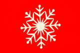 Close-up of white snowflake on red background
