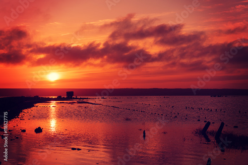 Beautiful sunny red colorful sunset on the lake with stones, wooden posts and reflection, natural seasonal summer vacation background