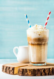 Latte macchiato with whipped cream in tall glass with two straws and pitcher on wooden board over blue painted wall background, selective focus, copy space, vertical composition