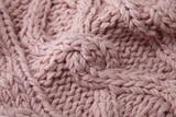 A full page close up of pastel pink knitted sweater fabric texture