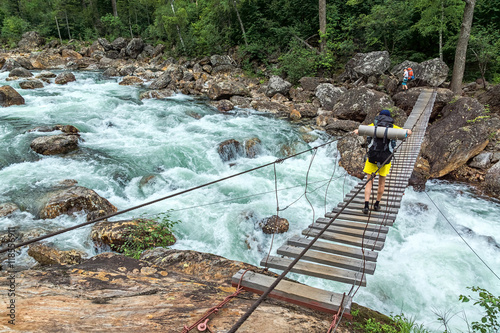 Poster Tourist passes on the suspension bridge over the Selenginka River