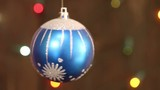 Blue Christmas ball on the background blinking blurred garland.
