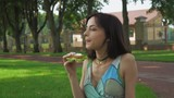 The girl brunette sits on the ground in the park and eat a sandwich and talking.