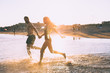 a couple is running on beach while the sun is set