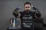 Tattoo artist holding ink machines