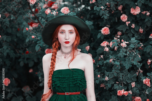 Plagát Red-haired girl with blue eyes and pale skin in a green hat and dress with a red belt