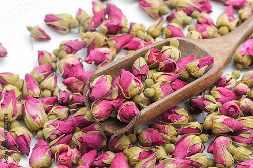 Zdjęcia na płótnie, fototapety, obrazy : Closeup roses flowers tea in a wooden scoop on a white backgroun