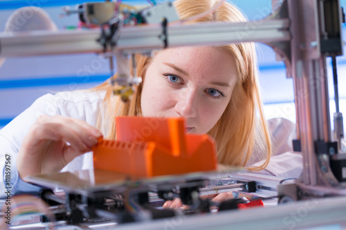 Young woman work with 3d printer