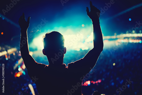 Man at concert dancing against lights background. Silhouette of man at music festival