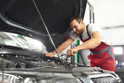 Automechaniker repariert Fahrzeug in einer Werkstatt // Auto mechanic repaired vehicle in a garage
