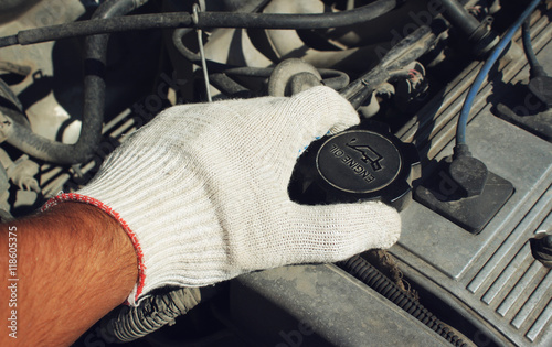 Fotobehang Stof The cover oil filler neck of the car in a hand
