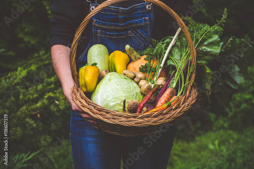 Woman farmer holding a basket of vegetables