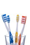 Bunte Zahnbürsten in einem Wasserglas. Isoliert auf weiß.