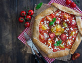 Whole wheat galette with tomatoes, feta cheese and fresh basil, overhead shot