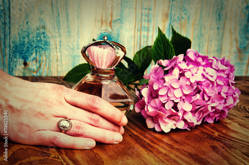 Poster Hand holding a perfume and hydrangea wooden background