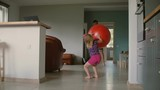 A back of a girl playing with a big red gym balloon with her father in the living room. Slow motion