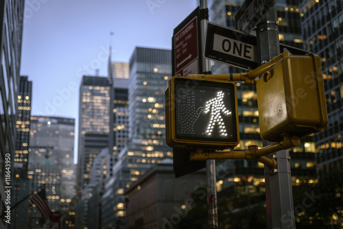 NYC crosswalk sign on busy one way street with sunset skyline in the background Poster