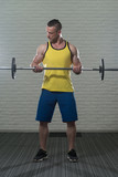 Biceps Exercise With Barbell On White Bricks Background