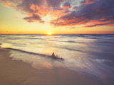 Sea landscape at sunset, sandy beach and cliff,waves breaking on the shore toned with a retro vintage effect