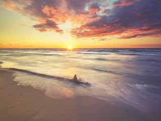 Fototapeta zachód słońca pod brzegiem morza