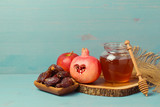 Honey, pomegranate, apple and dates on wooden board. Jewish New Year Rosh hashana celebration