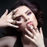 Portrait of a beautiful girl holding face in hands with rings on the fingers