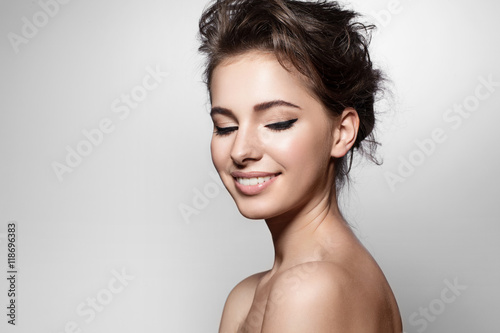 Plagát Beautiful woman with black arrows on eyes, clean skin and white teeth on grey ba