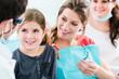 Zahnarzt mit schwangerer Frau und Kind in Praxis samt Sprechstundenhilfe