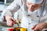 Koch oder Küchenchef beim Essen anrichten in Restaurant Küche - 118705579