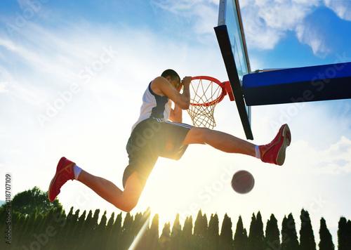 Poster Street basketball player performing power slum dunk.