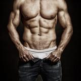 Mann mit muskulösen Körper öffnet seine Hose