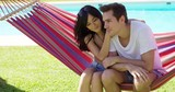 Affectionate young couple sitting on a colorful stripes hammock in the shade of a tree at the side of a swimming pool watching something intently off screen.