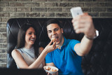 Attractive young couple having good time in cafe restaurant. Young man holding a cellphone and making selfie.